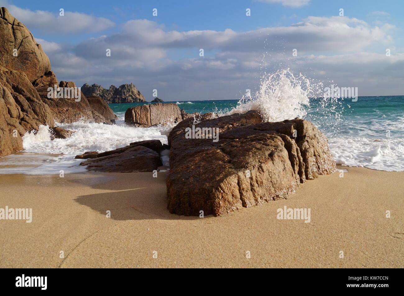 Crashing waves over a large rock on Porthcurno Beach - Stock Image