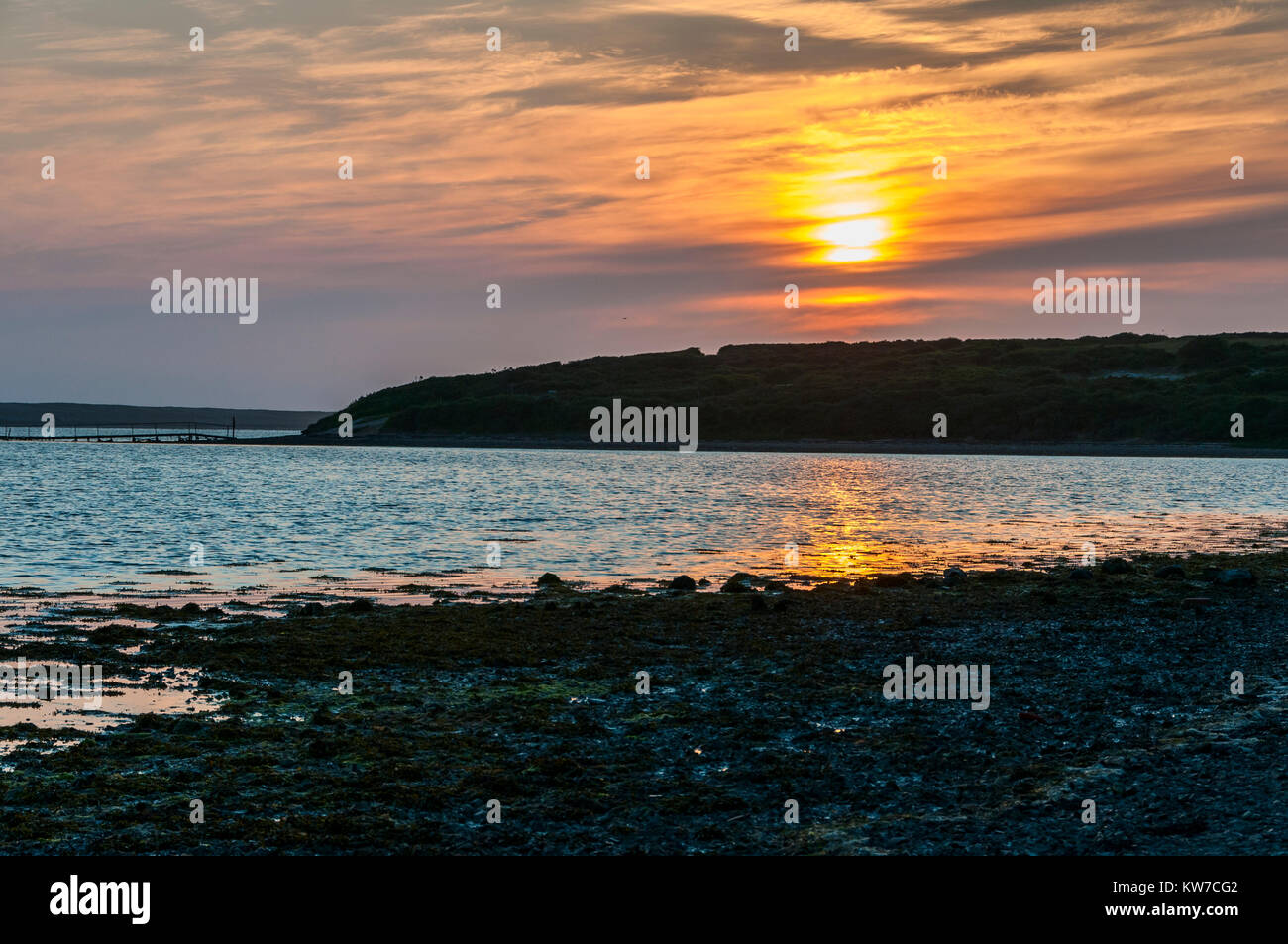 The surface of the Fleet Lagoon reflects some of the spectacular warm orange tones of sunset across the sky as darkness - Stock Image