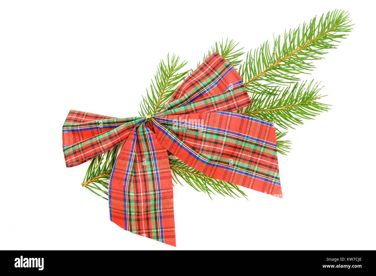 Christmas decorations concept - red checkered bow on a spruce twig on a white background in close-up - Stock Image