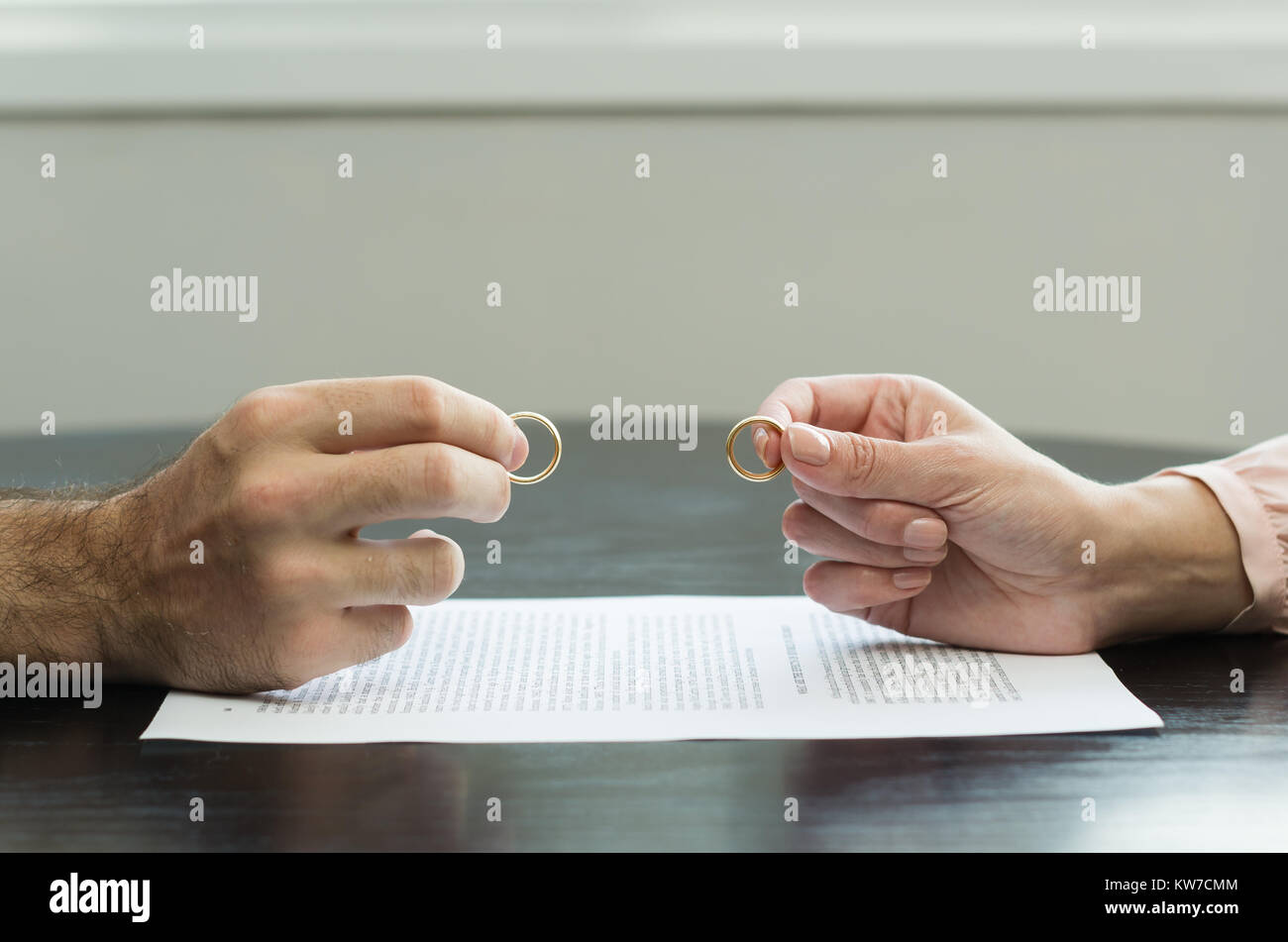 Great concept of divorce, end of relationship, hand of man and woman handing over alliances, divorce agreement. - Stock Image