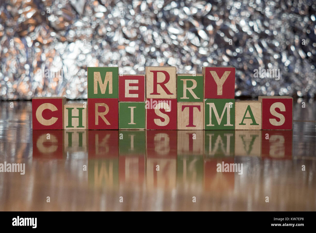 Wood blocks in green, red and light wood with capital letters spelling Merry Christmas. Photographed with a shallow - Stock Image