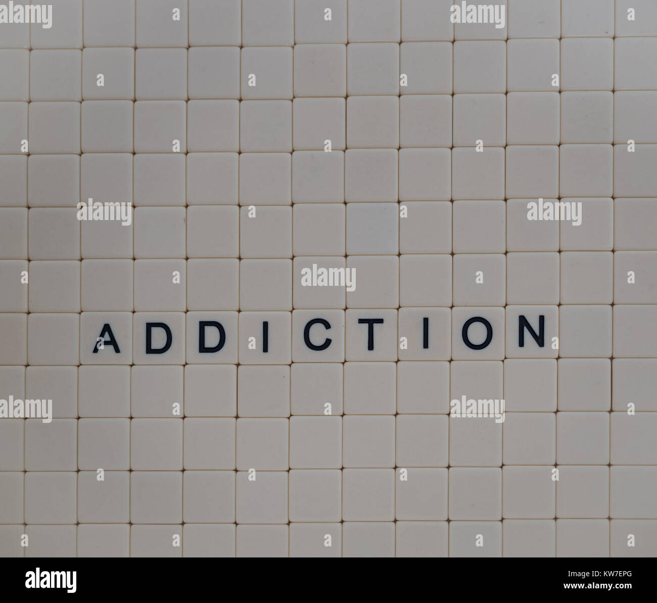 Addiction spelled in black capital letters on beige tiles with a background of off white tiles. Photographed from - Stock Image