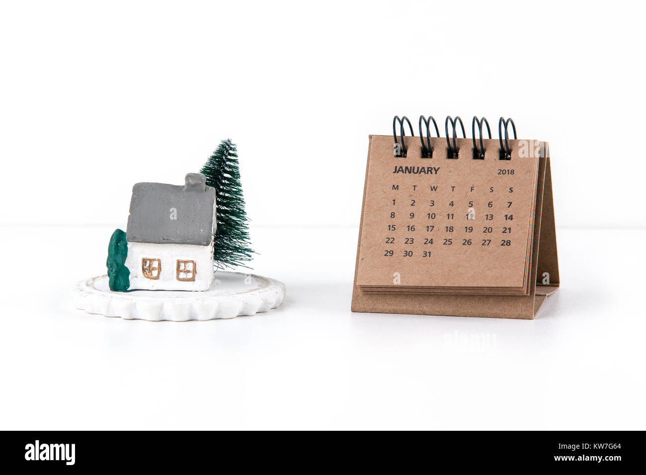 Little house model and tree on white background with calendar 2018 and month of January - Stock Image
