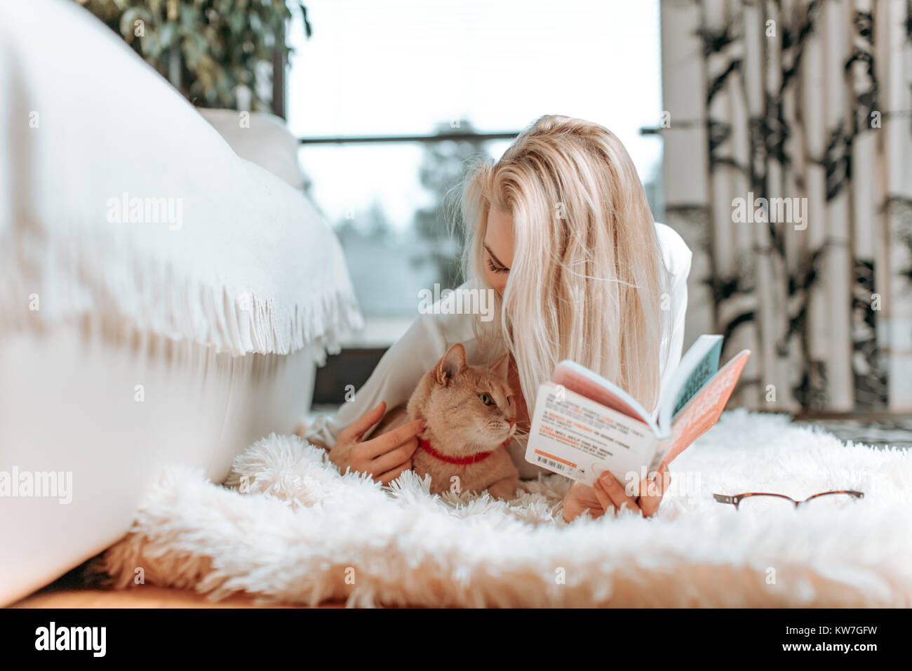 Beautiful young blonde female student studying or reading a fascinating book novel, on her white, leather sofa - Stock Image