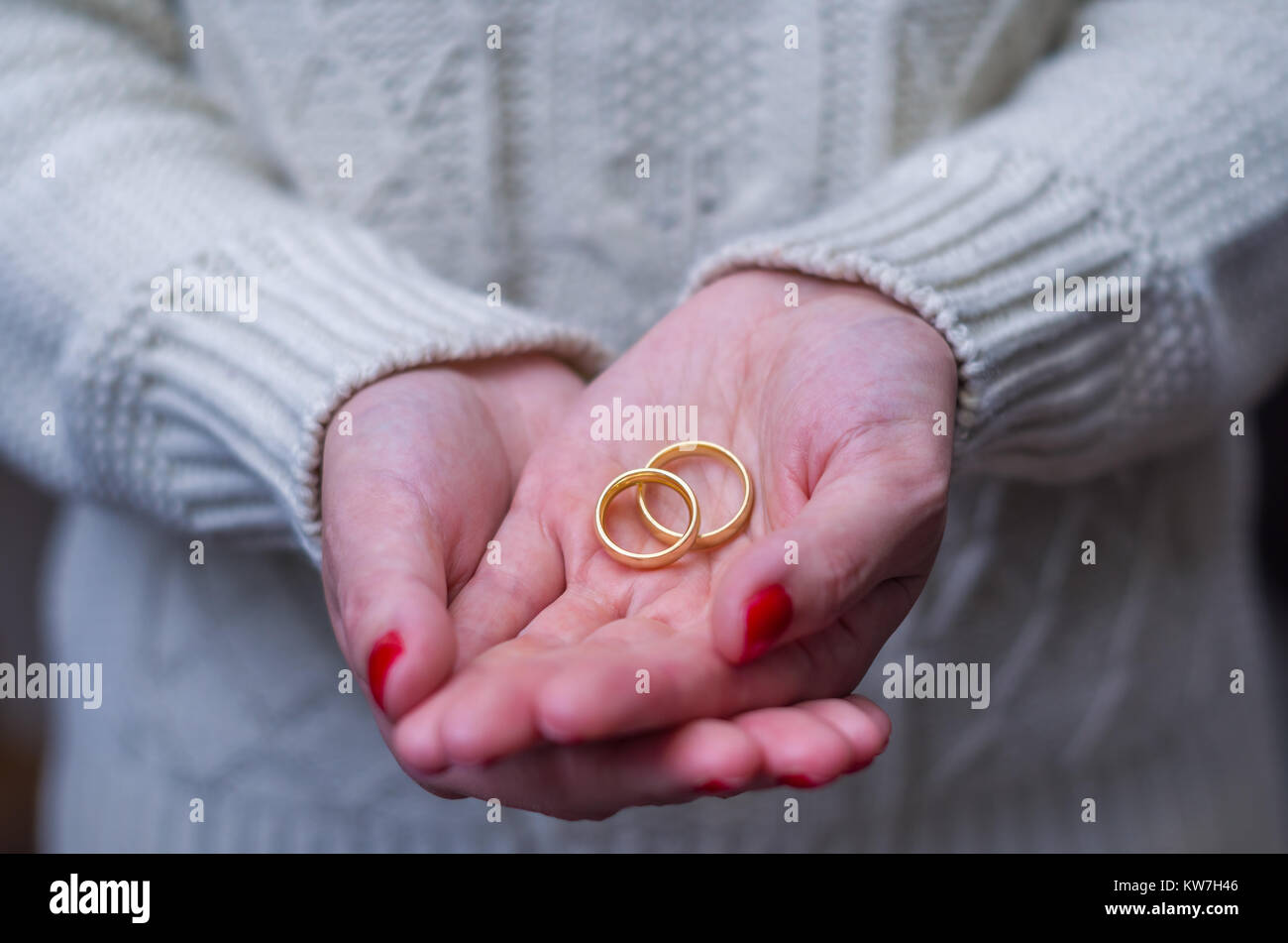 Great concept of divorce woman hand with two gold wedding rings in ...