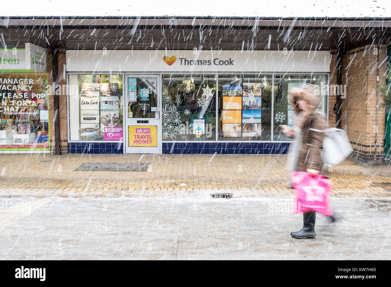Woman walks past exterior of branch of  Thomas Cook Travel Agency in winter snow - Stock Image