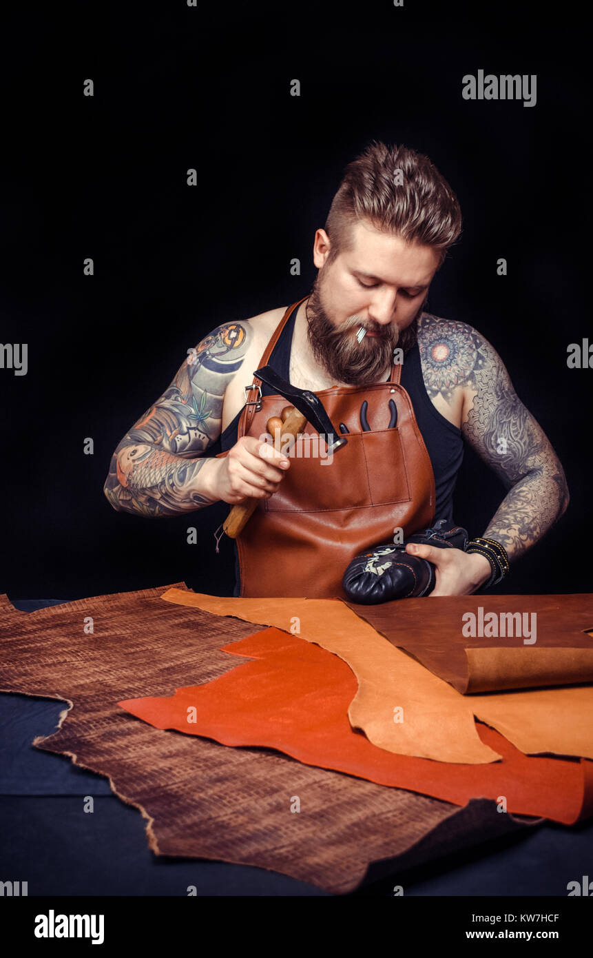 Portrait of shoemaker hammering on a shoe - Stock Image