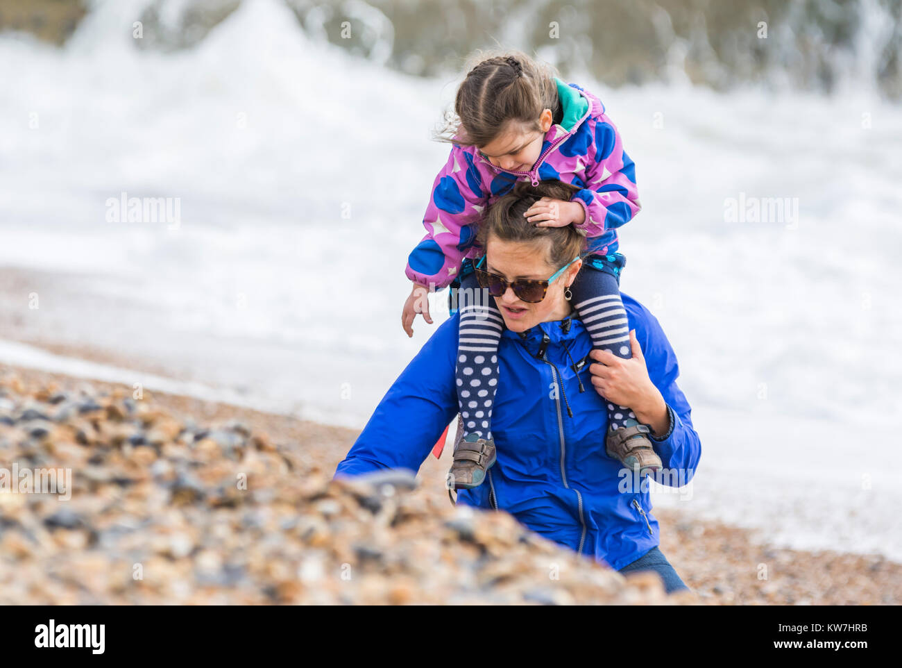 Child on woman's shoulders collecting shells on a beach on a rough day in the UK. - Stock Image