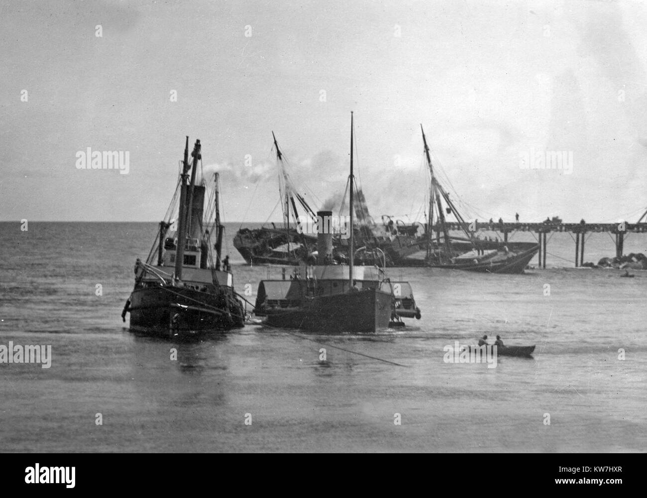 A paddle steamer and another boat pass the stranded Hawea, which was wrecked on the North Tiphead while leaving - Stock Image