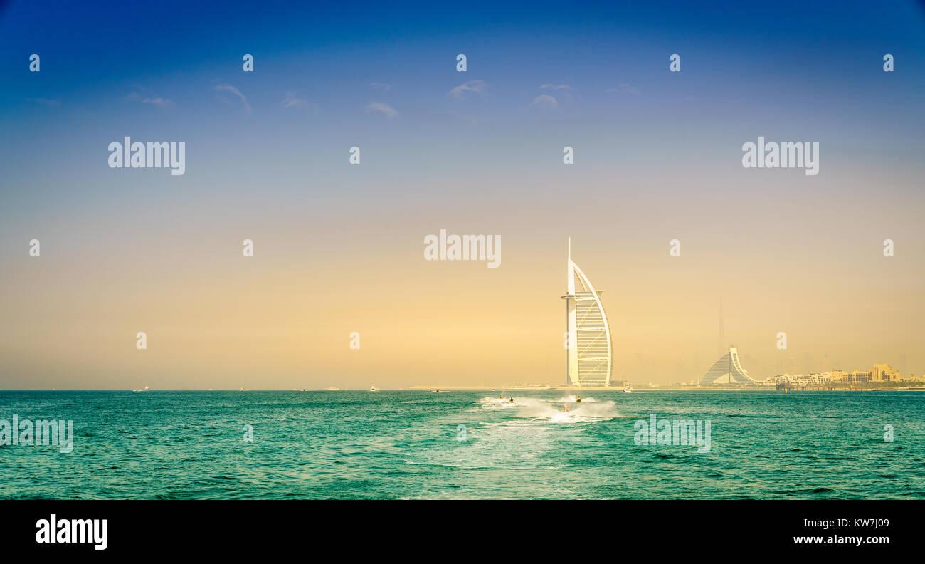 Jetskis near Dubai coast with Burj Al Arab and Jumeirah Beach hotels in the backdrop - Stock Image