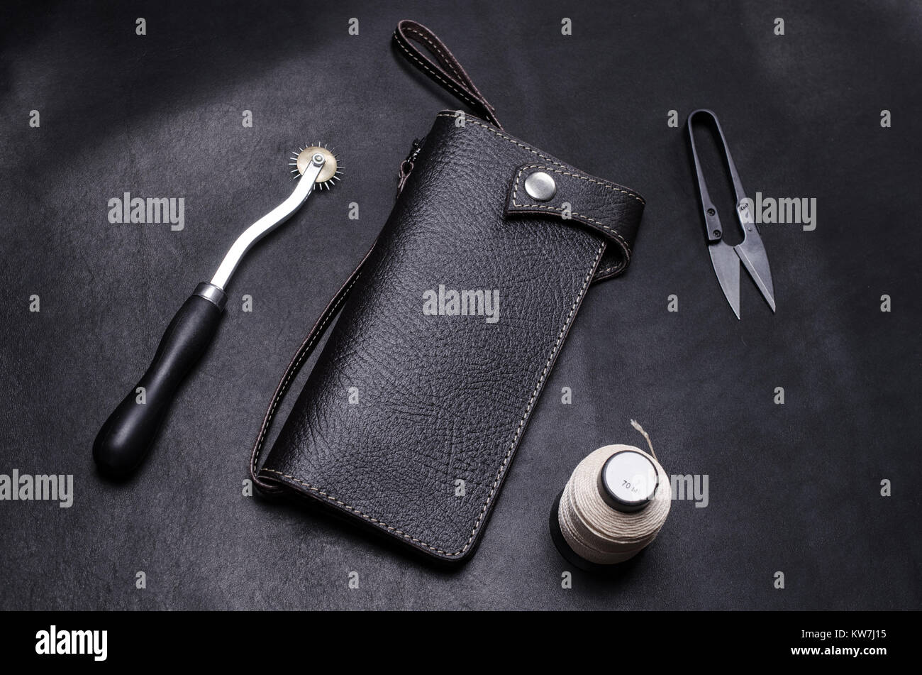 craft tools and leather purse on a black work table. - Stock Image