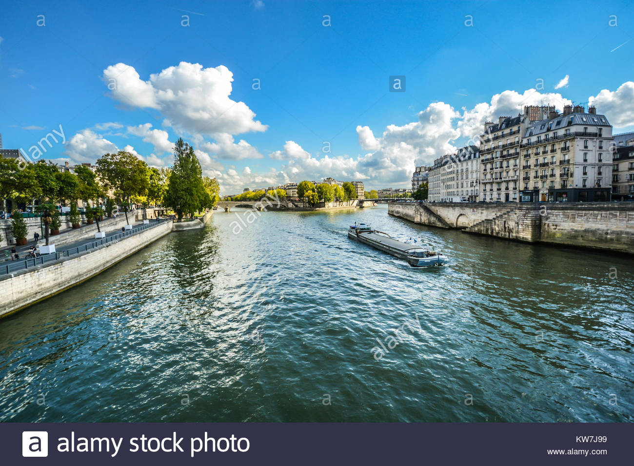 Sunny day view from the Pont d'Arcole near Ile de la Cite as a cruise boat floats down the River Seine - Stock Image