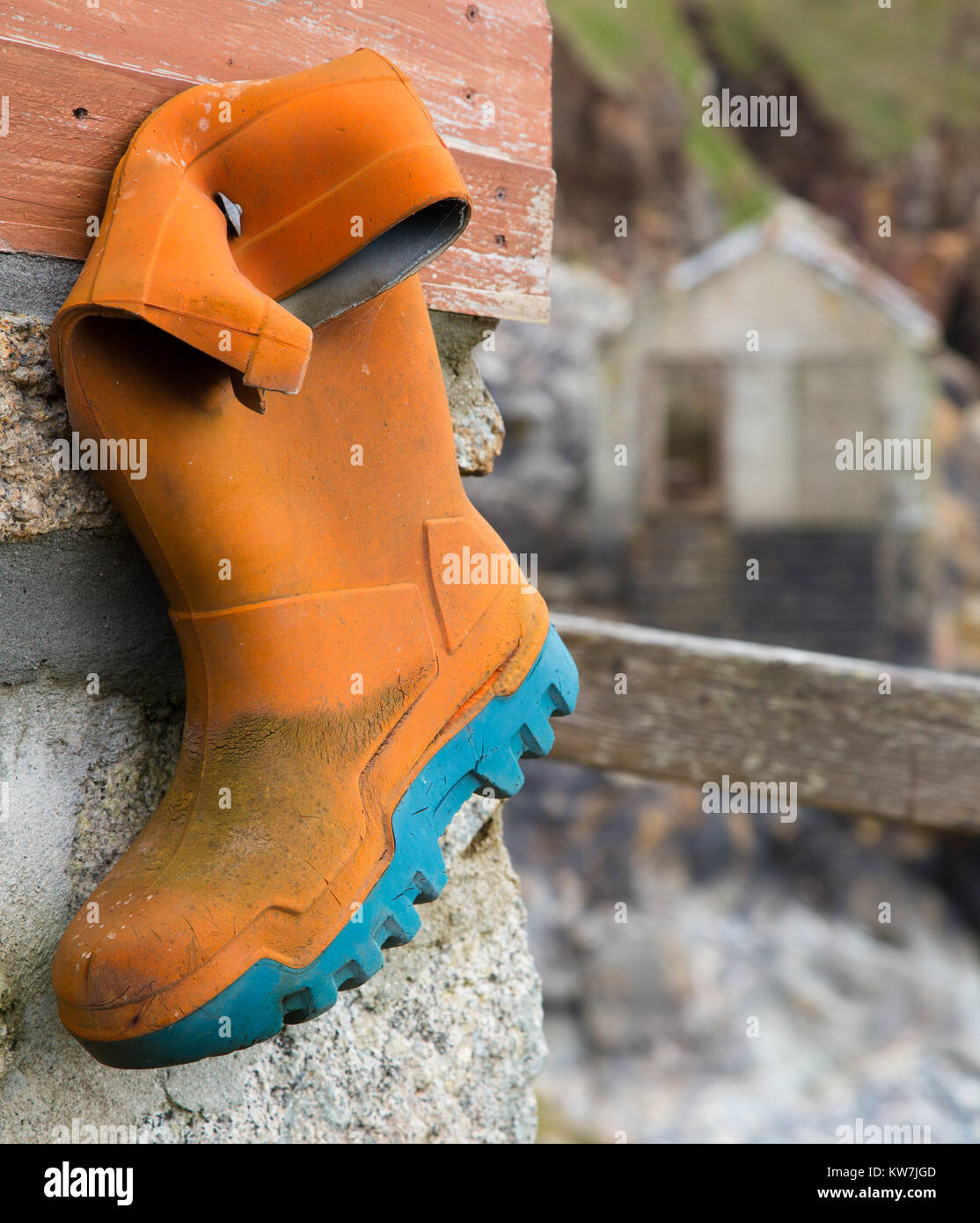 Welly Boot is Nailed to a wall besides the coast Stock Photo