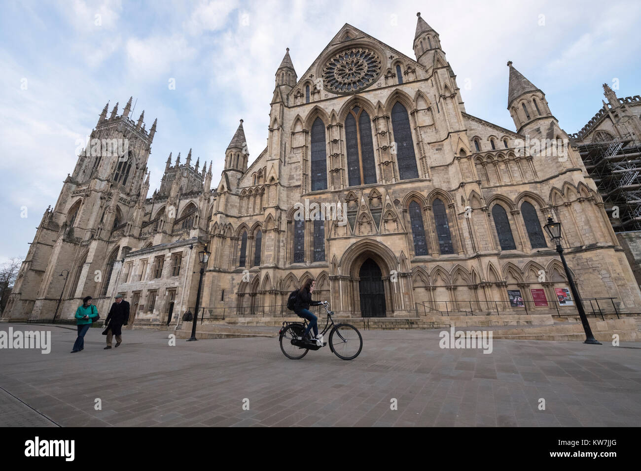 York centre - south entrance to magnificent York Minster from piazza where people walk & female on phone cycles - Stock Image