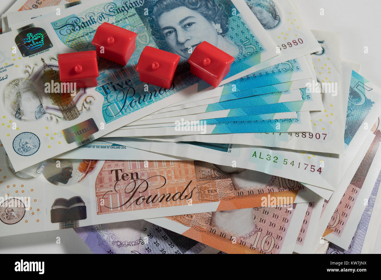 5, 10 and 20 Pound notes randomly arranged with red monopoly hotels - Stock Image
