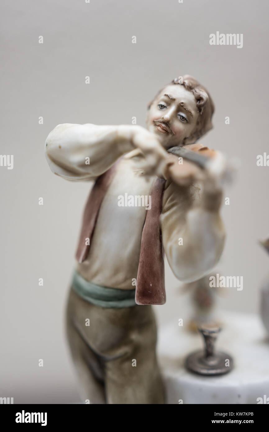 Antique ceramic statue of man and woman at restaurant scene - Stock Image
