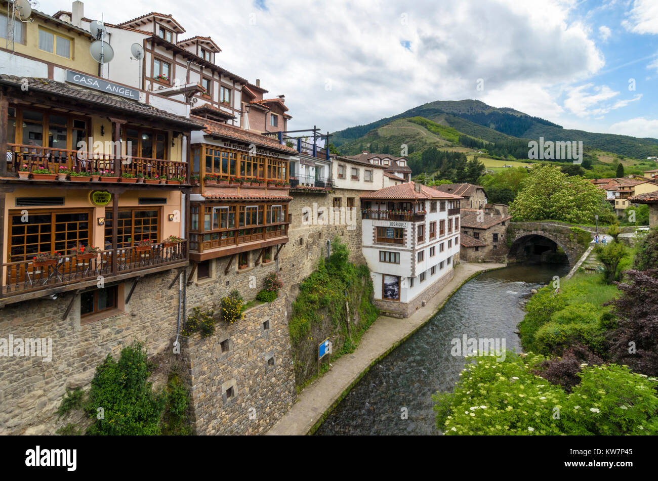 Potes Town hanging old buildings over the Rio Quiviesa, Potes, Cantabria, Spain - Stock Image