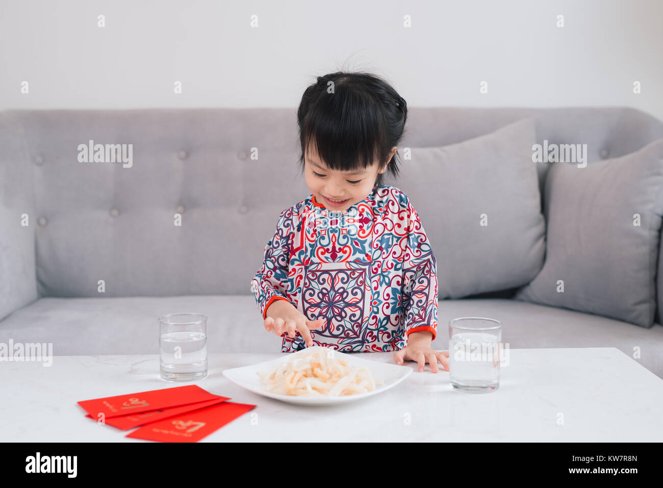 Vietnamese small girl in Ao Dai Traditional dress, celebrate new year at home. Tet Holiday. Stock Photo