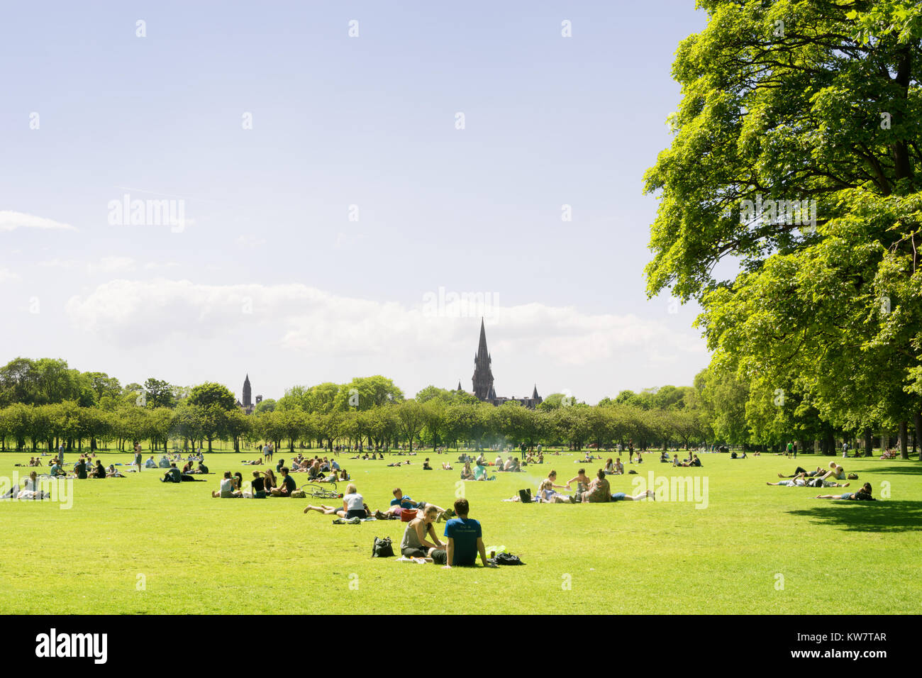 Young people, students of Edinburgh University enjoy a sunny day in the Meadows, Edinburgh, Scotland, UK, sunbathing - Stock Image