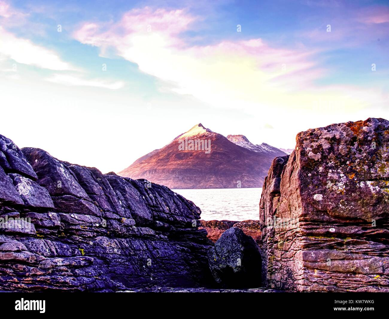 The stony beach and cliff of rocky bay. Blue tones of February sunset, pink horizon.  Dark slipery boulders with - Stock Image
