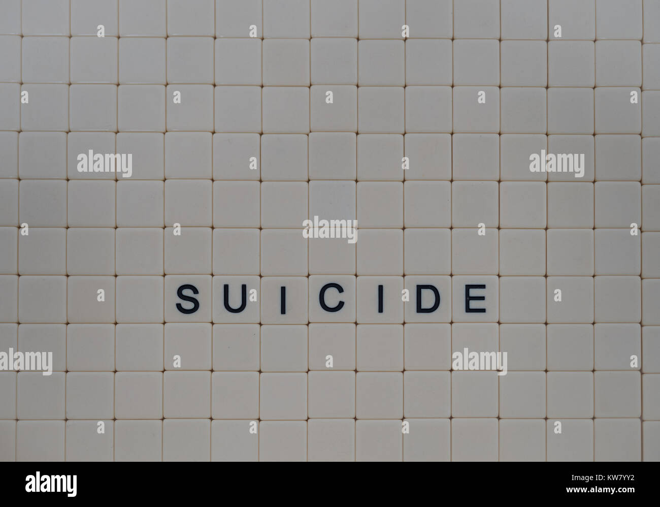 Tan tiles with black capital letters spelling Suicide set in a background of small tan tiles.  Image has copy space. - Stock Image