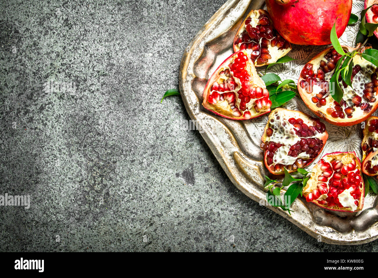 Ripe pomegranates on a steel tray. On a rustic background. - Stock Image