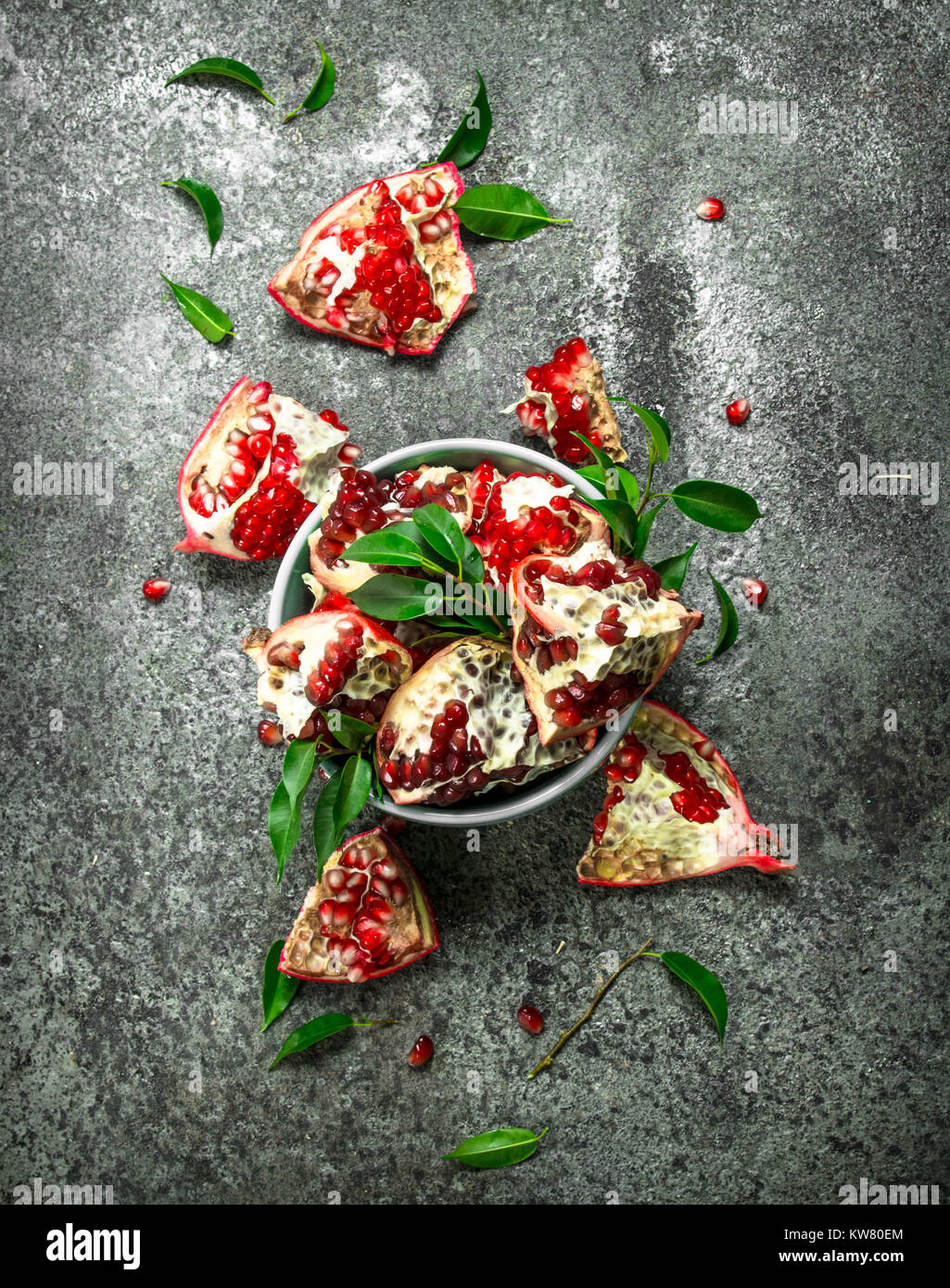 Ripe pieces of pomegranate in a bowl. On a rustic background. - Stock Image