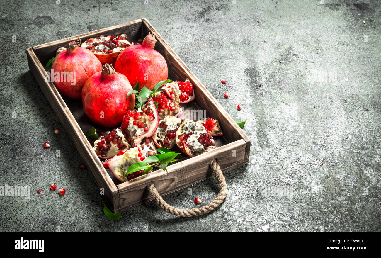 Fresh pomegranates on a wooden tray. On a rustic background. - Stock Image