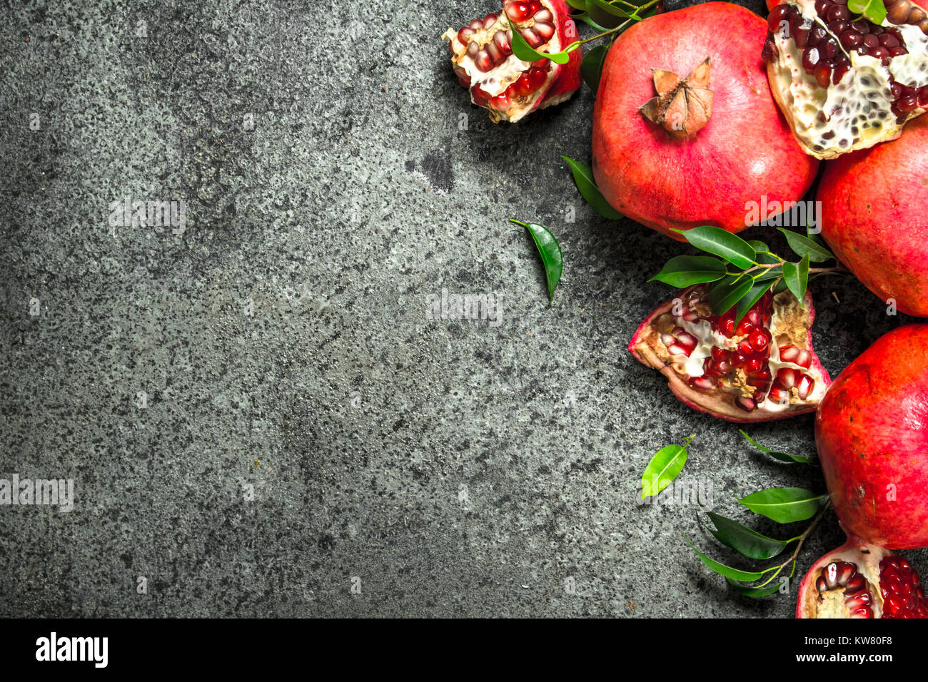 Ripe pomegranates with leaves. On a rustic background. - Stock Image