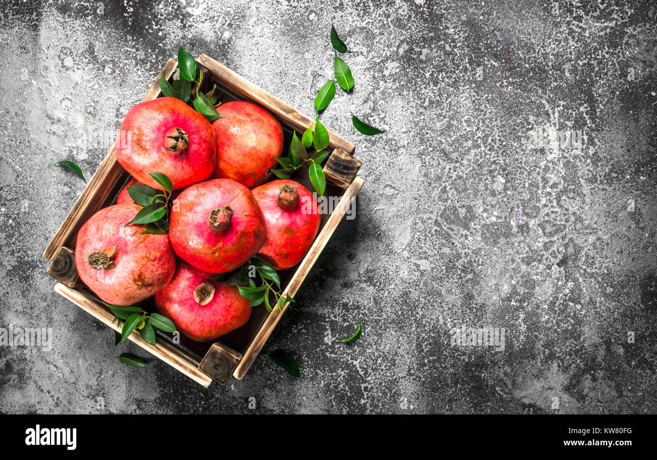 Ripe pomegranates in a box. On a rustic background. - Stock Image