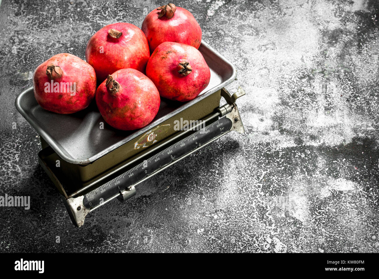 Ripe pomegranates on the scales. On a rustic background. - Stock Image