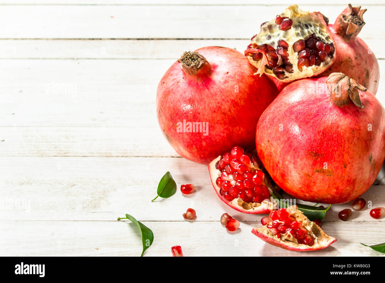 Ripe pomegranates with leaves. On a white wooden table. - Stock Image