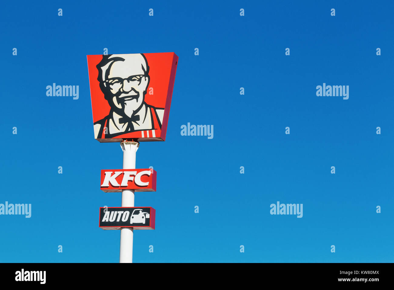 KFC logo over blue sky. KFC is an American fast food restaurant chain that specializes in fried chicken - Stock Image