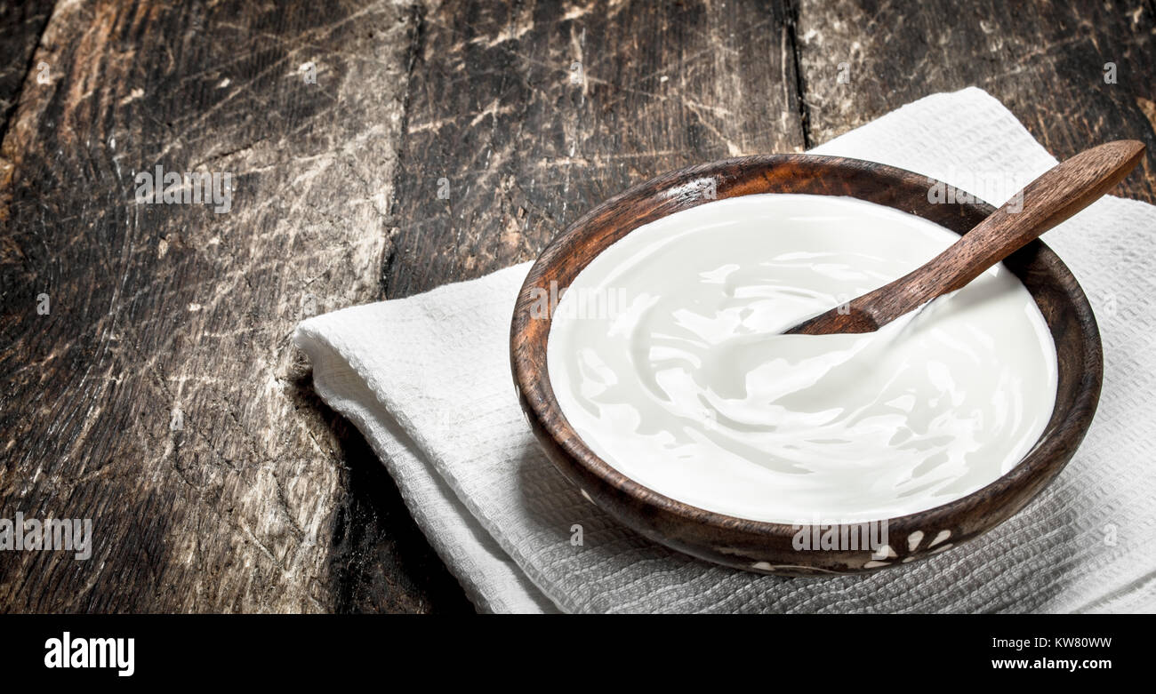Natural yogurt in a bowl. On a wooden background. - Stock Image