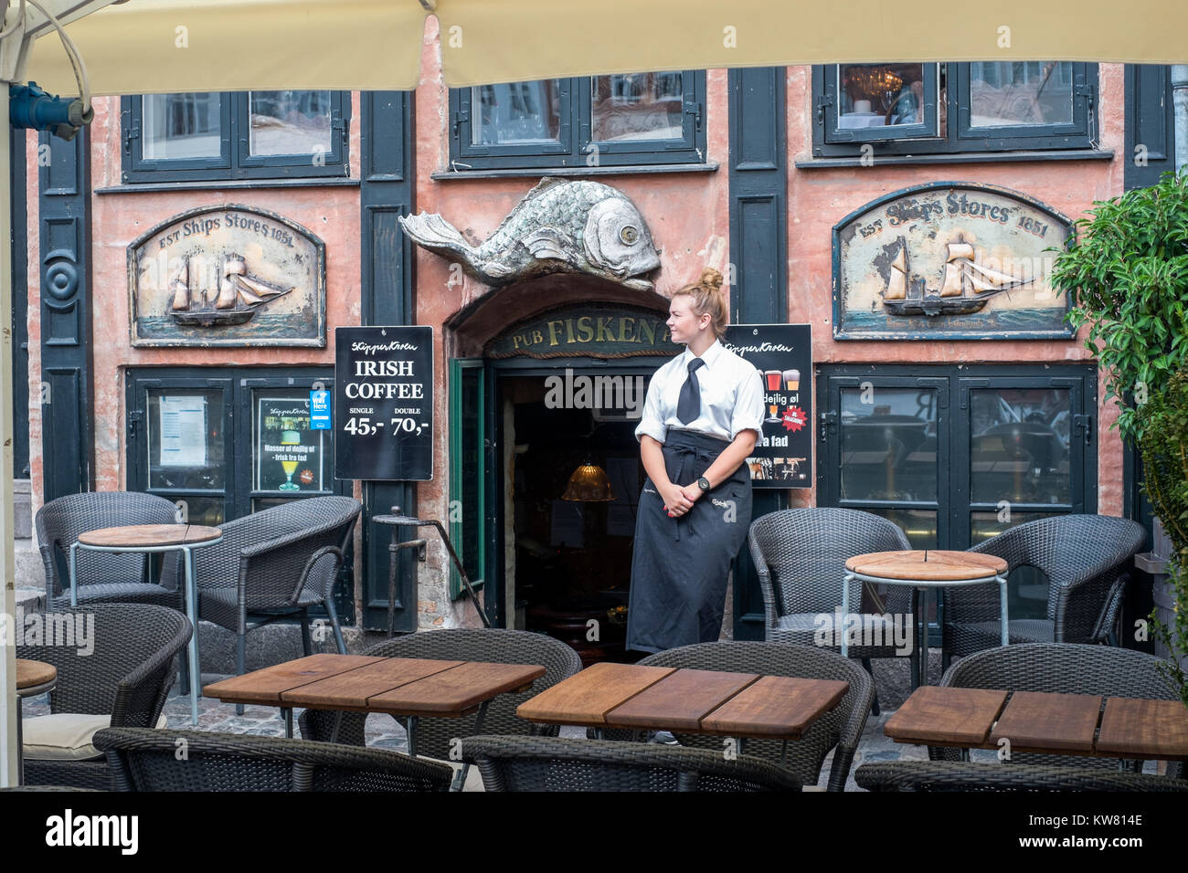 Waitress outside a waterfront restaurant at Nyhavn, a 17th century harbor district in the center of Copenhagen and - Stock Image