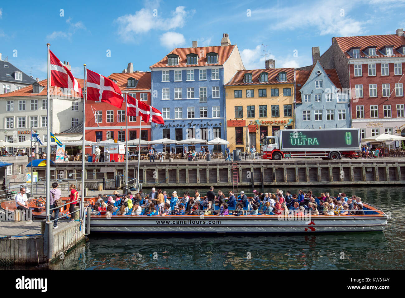 Tour boat in Nyhavn, a 17th century harbor district in the center of Copenhagen and currently a popular tourist - Stock Image