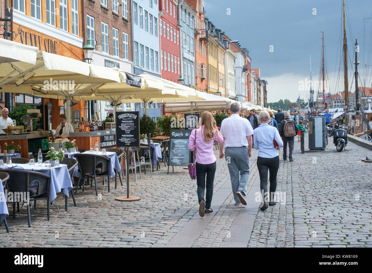 Waterfront restaurants at Nyhavn, a 17th century harbor district in the center of Copenhagen and currently a popular - Stock Image