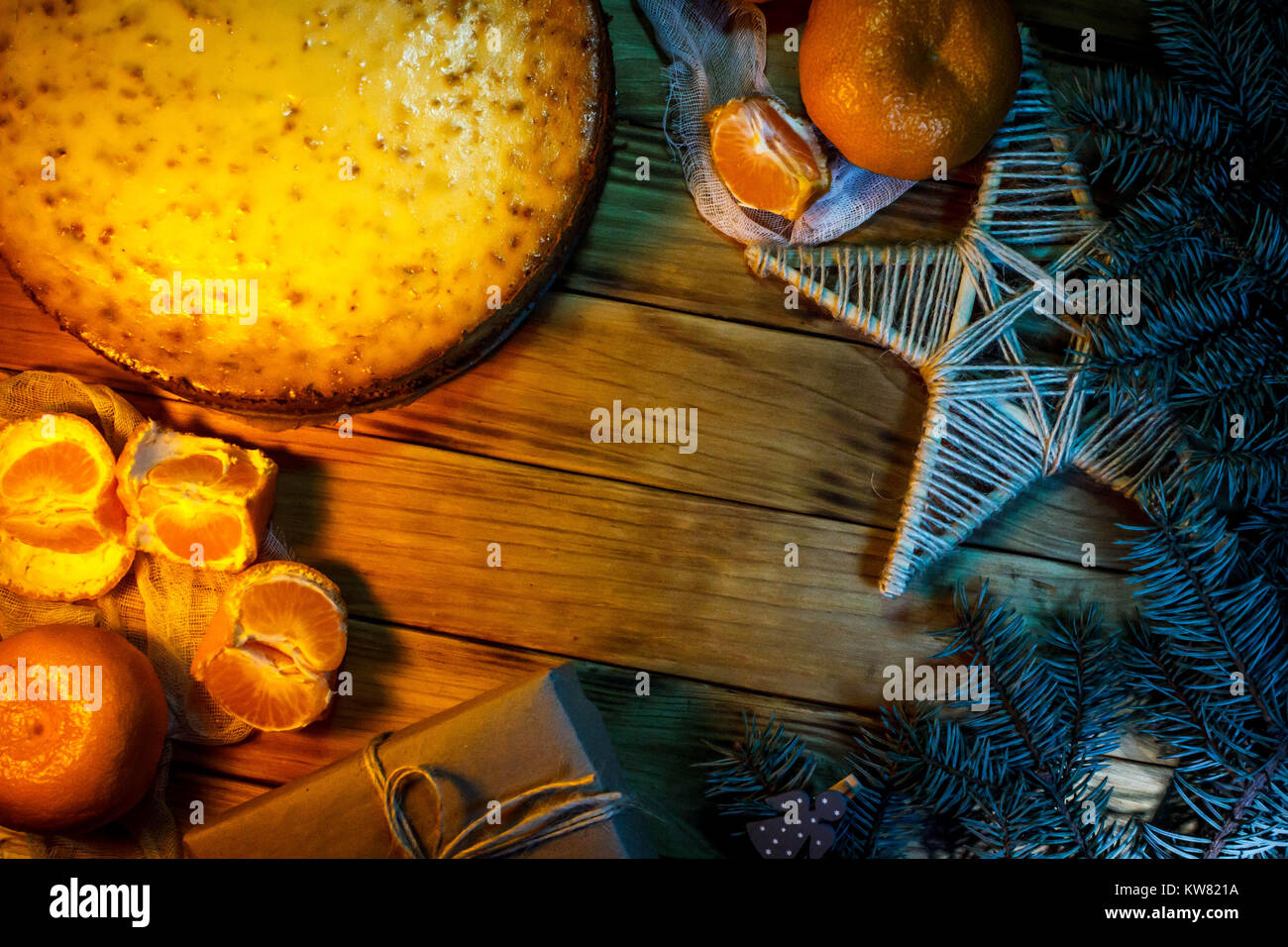 Cheese cake against wooden background with oranges, gift box and christmas decoration. Stock Photo