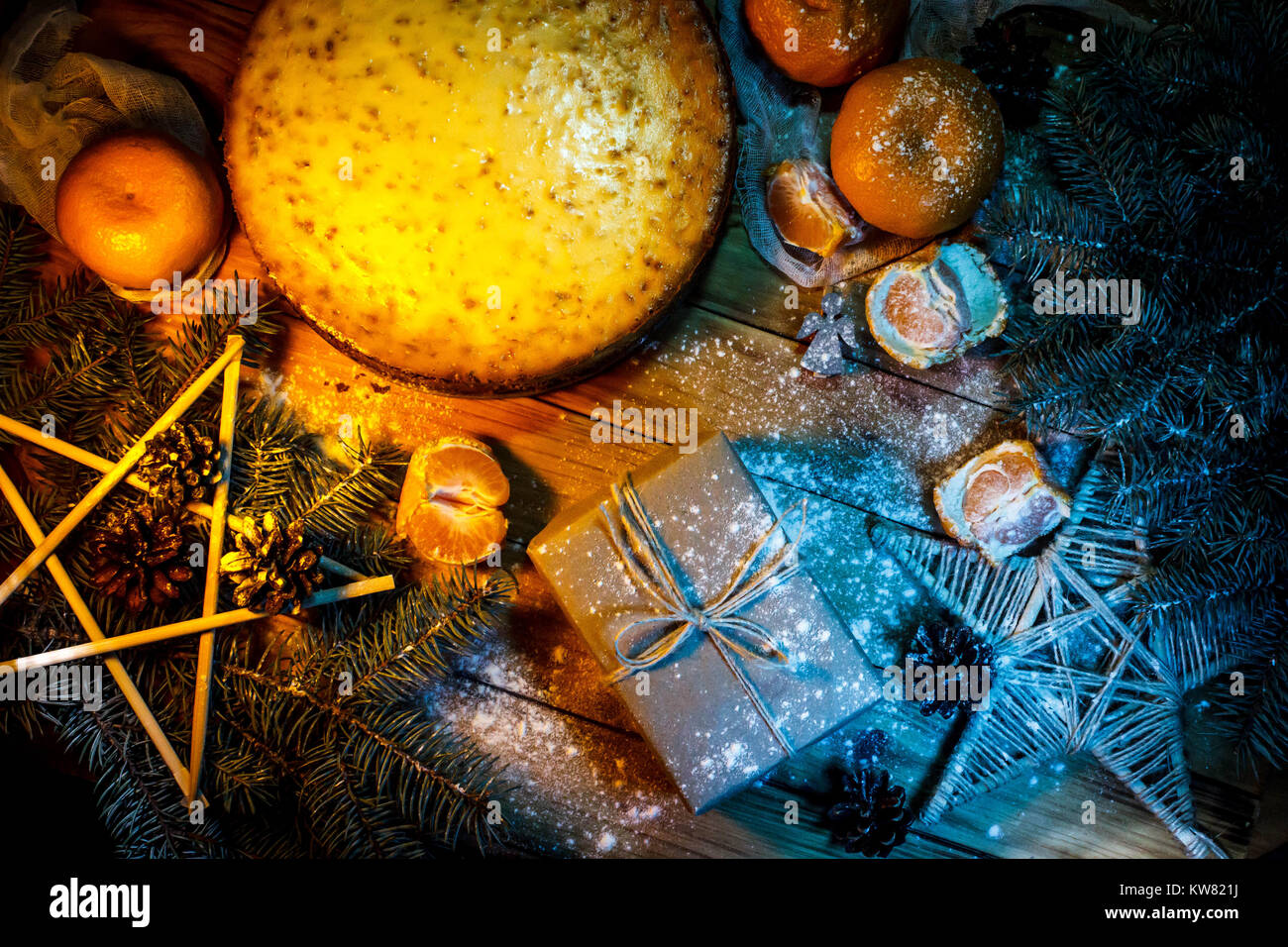 Cheese cake against wooden background with oranges, gift box and christmas decoration. - Stock Image