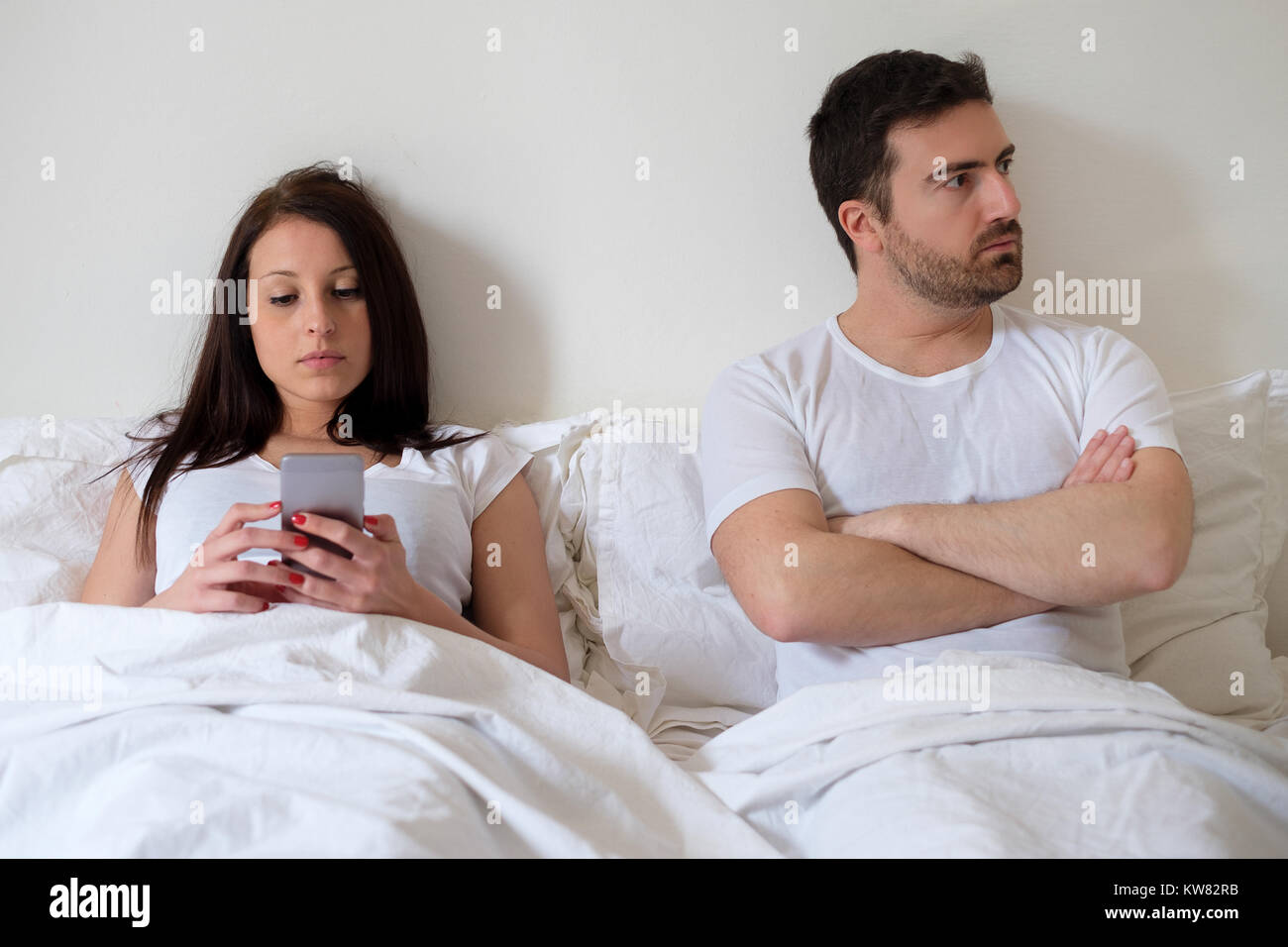 Bored couple and worried man by his wife smartphone addiction - Stock Image