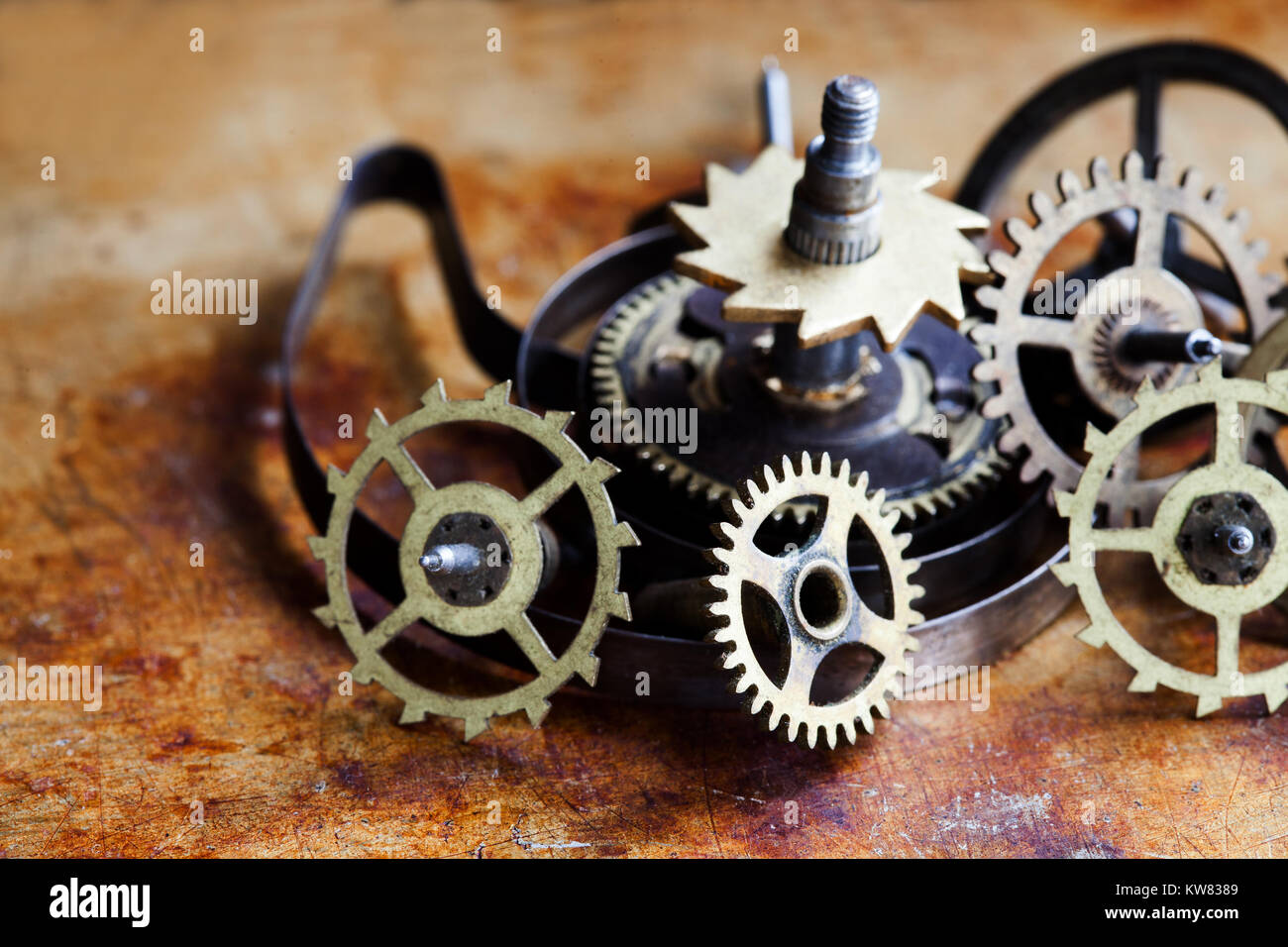 Antique clock mechanism steampunk style cogs gears wheels macro view. Vintage rusty metal surface background, shallow - Stock Image
