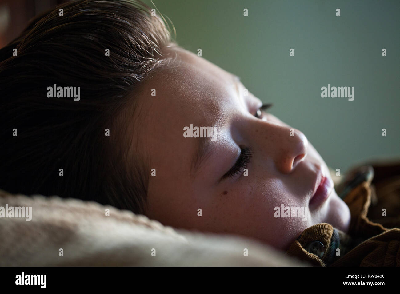 Handsome little boy with chubby cheeks and brown pompadour hair laying in bed and relaxing with the afternoon sunlight Stock Photo