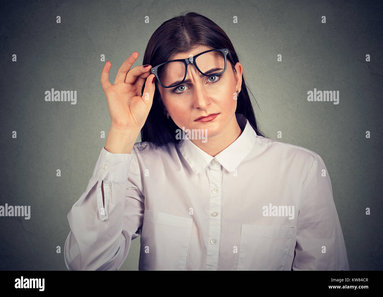 Young woman lifting eyeglasses while looking at camera with surprise. - Stock Image