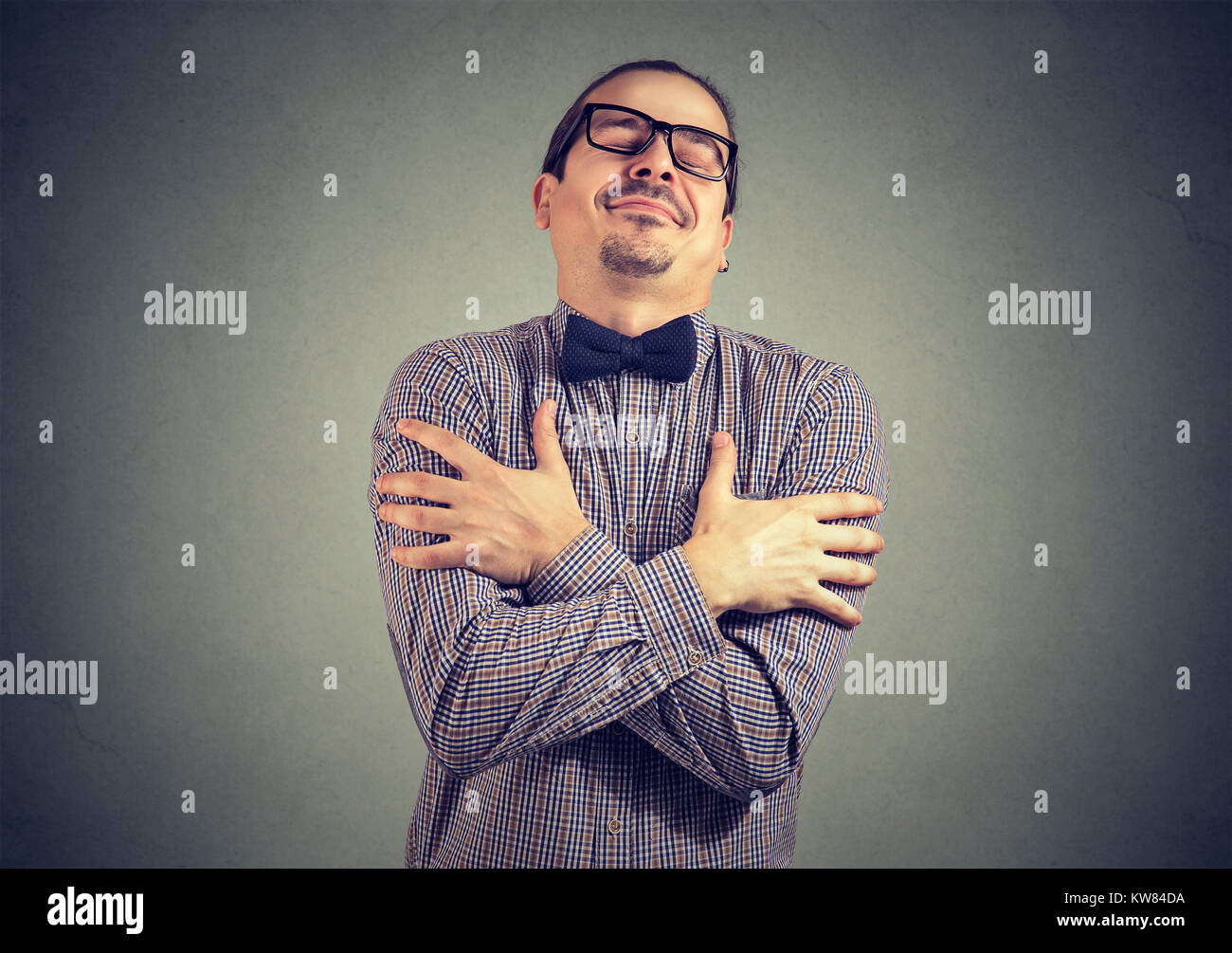 Young stylish man in bow-tie and eyeglasses embracing himself with great feeling of love. - Stock Image