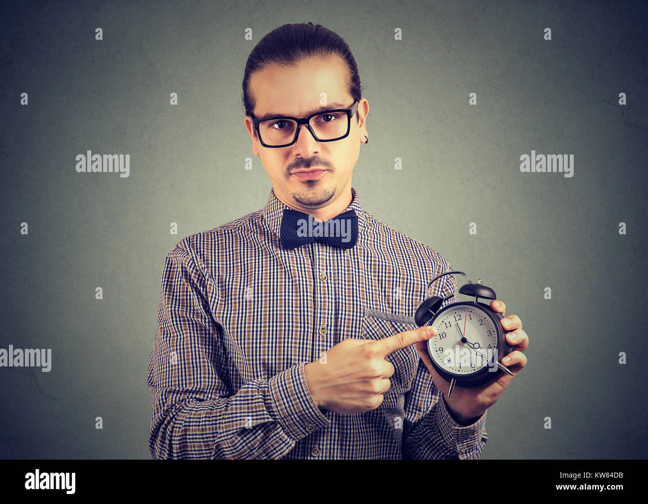 Formal man in eyeglasses reminding about punctuality pointing at clock and looking at camera. - Stock Image