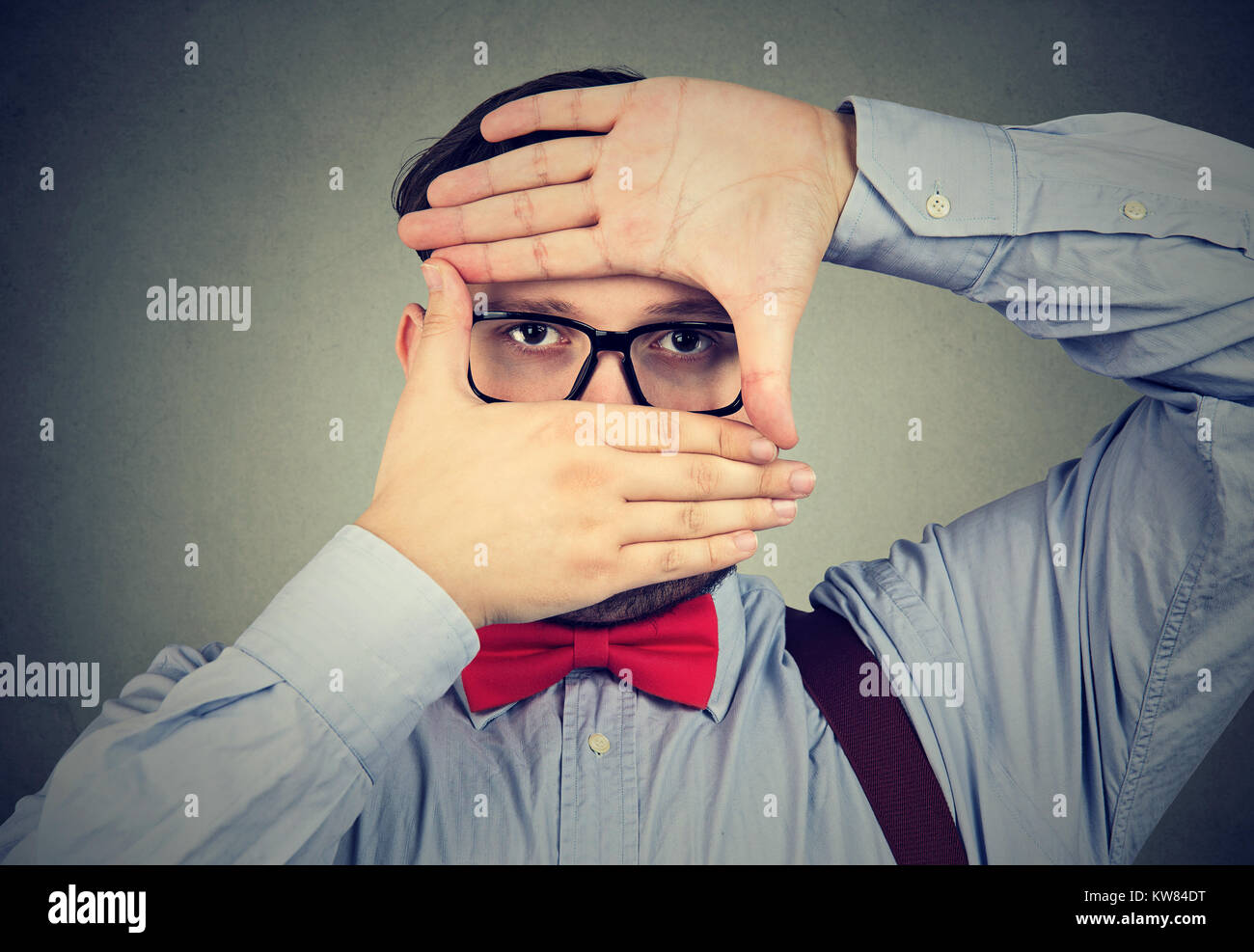 Chunky man making frame and looking at camera with limited vision. - Stock Image