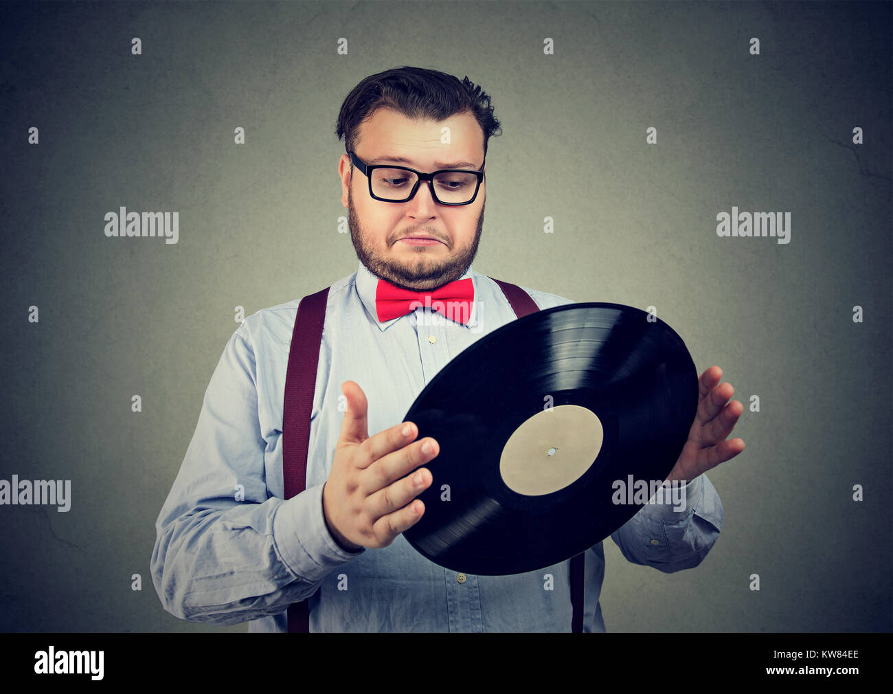 Chunky man in formal outfit holding old vinyl disk looking confused. - Stock Image