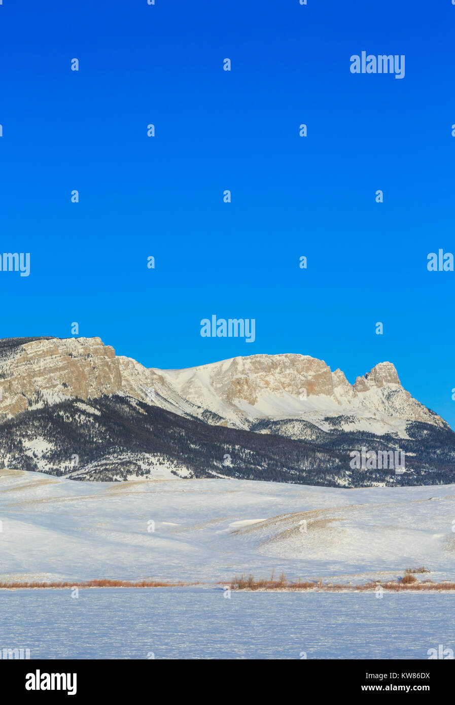 sawtooth ridge along the rocky mountain front above frozen anderson lake in winter near augusta, montana - Stock Image