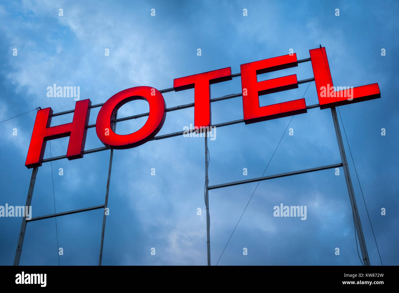 Large illuminated hotel letters sign against a blue sky - Stock Image