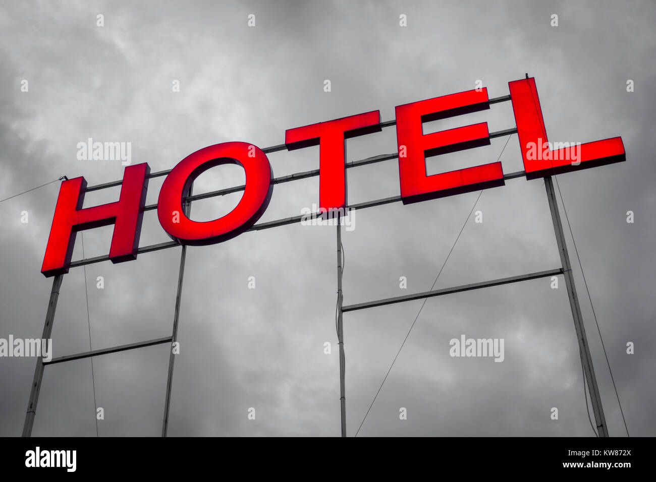 Large illuminated hotel letters sign against a grey / black & white B&W sky - Stock Image